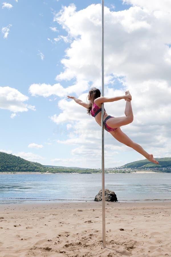 Morena acrobática do desempenho no roupa de banho no polo para dançar fotografia de stock