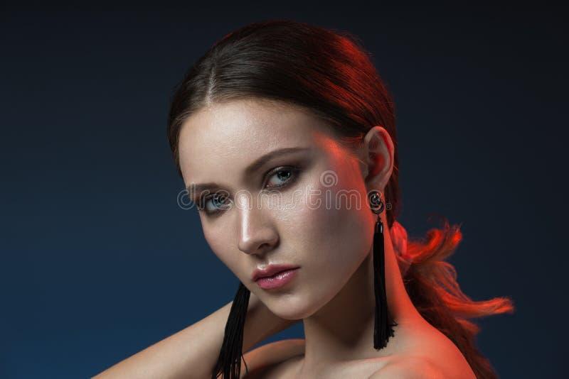 A morena adulta do encanto com compõe em luzes vermelhas e azuis no st foto de stock