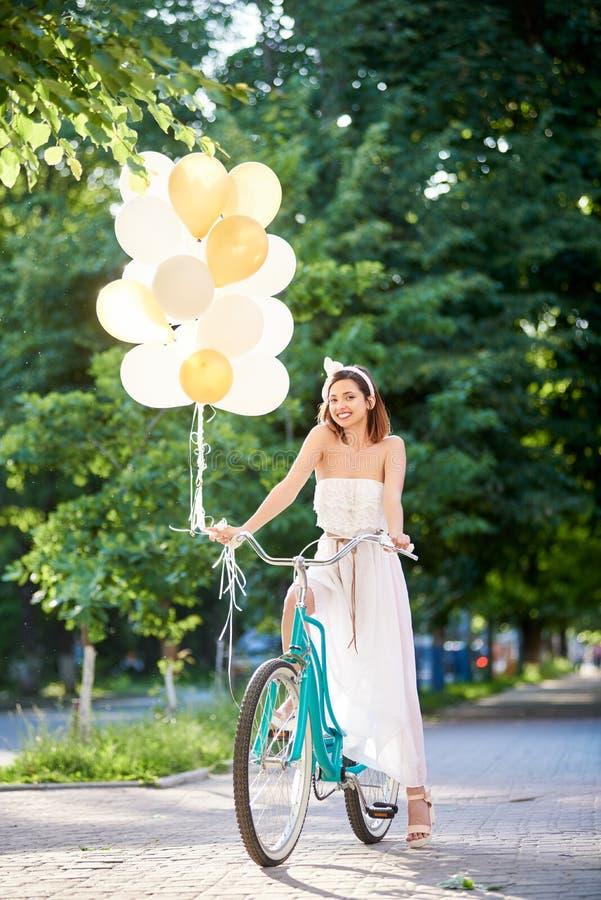 Morena atrativa de sorriso que guarda ballons ao conduzir a bicicleta azul na aleia do parque imagens de stock