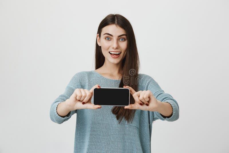Morena atrativa e esperta que sorri amplamente ao fazer a propaganda do smartphone novo, guardando a com ambas as mãos fotografia de stock