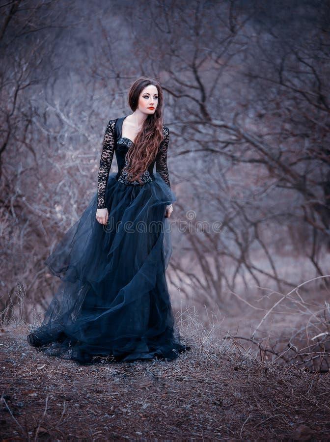 Morena atrativa lindo, senhora em um vestido preto longo com os braços e os ombros abertos desencapados, menina apenas no outono fotografia de stock