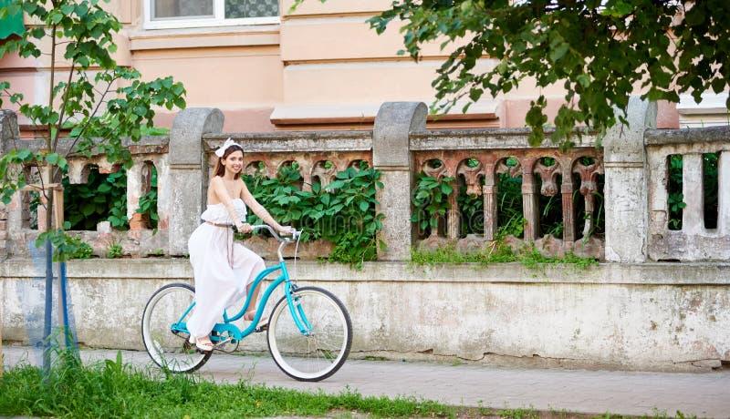 Morena atrativa no vestido branco que monta a bicicleta azul que passa a cerca velha decorada com árvores e arbustos fotografia de stock royalty free