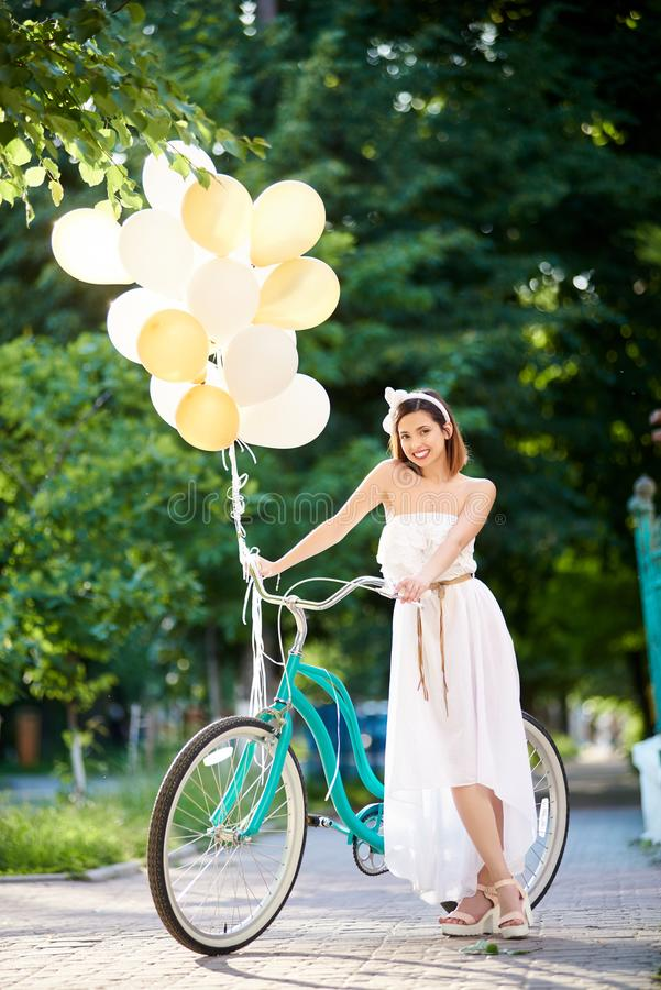 Morena atrativa positiva no vestido branco que levanta com baloons perto da bicicleta azul em um parque foto de stock