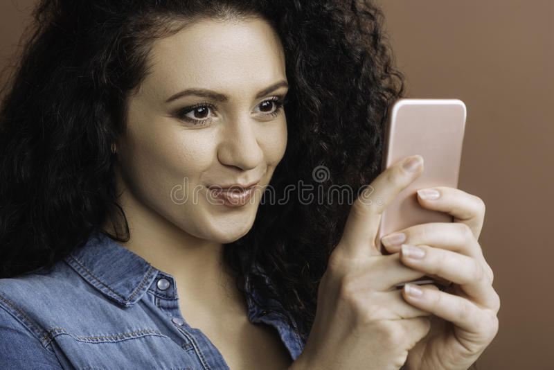 Morena atrativa usando seu telefone celular foto de stock