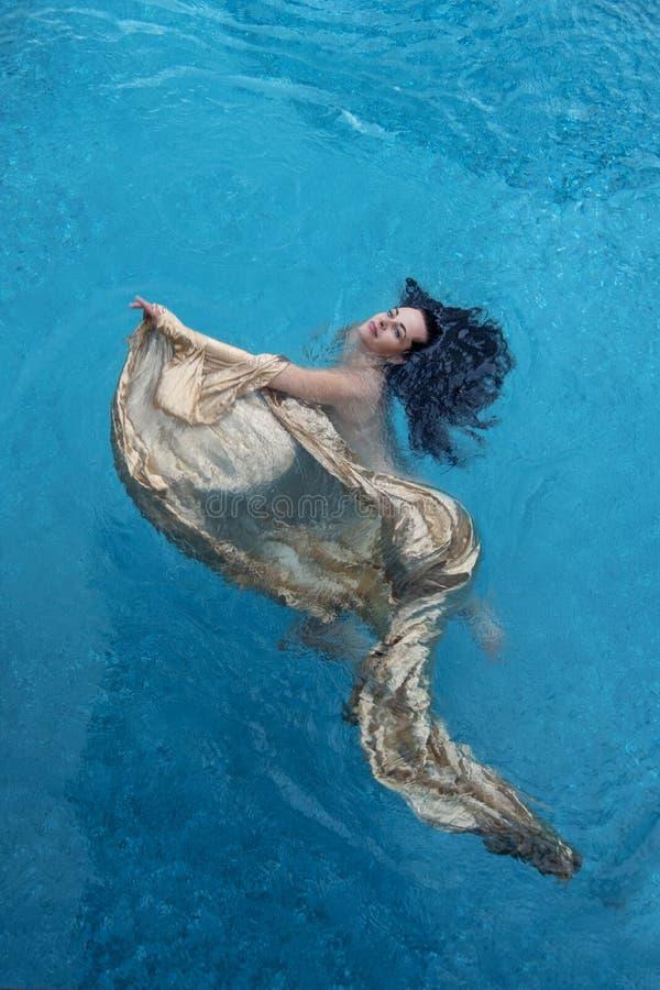 Morena bonita com as ondas relaxadas nos flutuadores dourados de toalha que flutuam felizmente na associação dos termas na água a imagem de stock