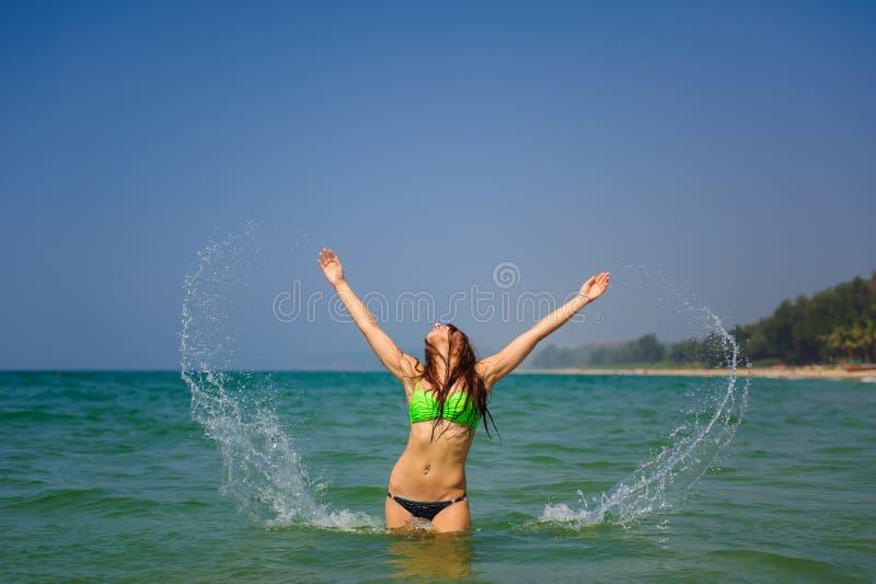 A morena bonita com cabelo longo está cintura-profunda no oceano e espirra suas mãos na água Menina delgada nova imagem de stock royalty free