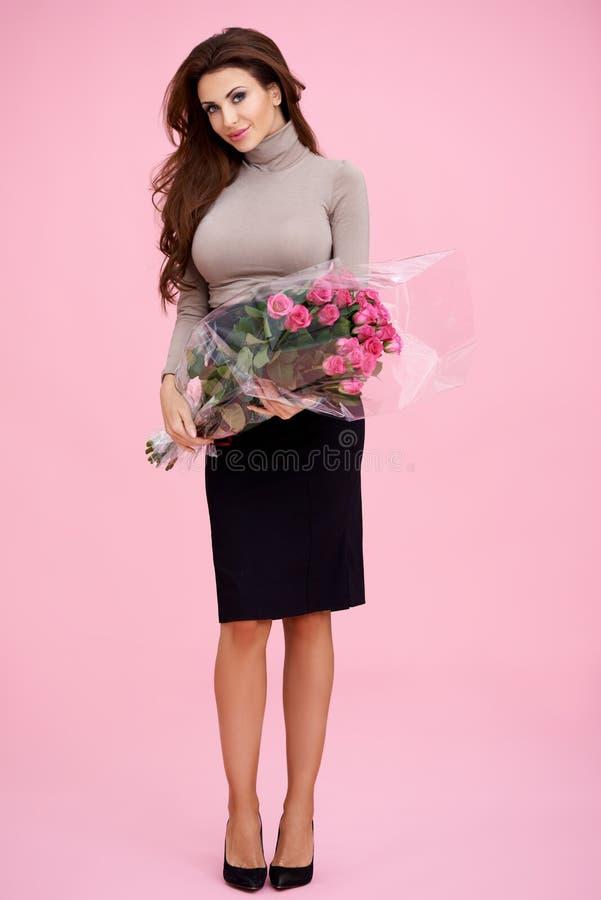 Morena bonita com grupo de rosas cor-de-rosa imagens de stock royalty free