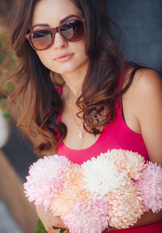 Morena bonita com um ramalhete de flores cor-de-rosa imagem de stock