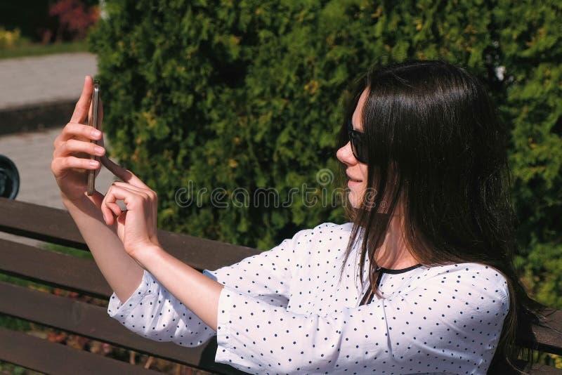 A morena bonita da mulher faz o selfie com o telefone celular que senta-se no parque fotos de stock royalty free