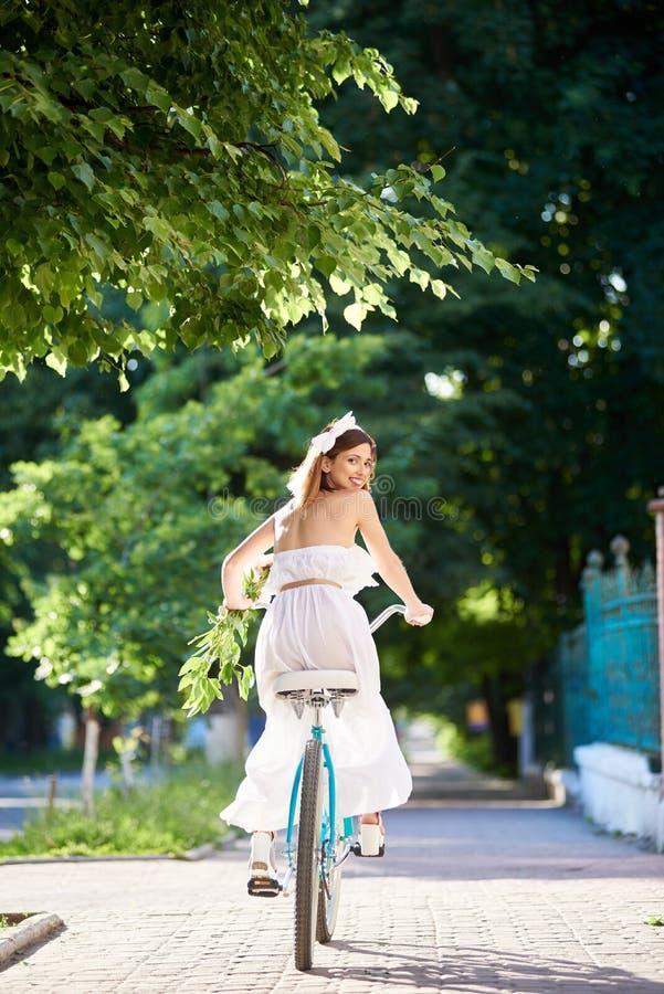 A morena bonita feliz olha para trás a astúcia que monta a bicicleta azul esverdeia para baixo a aleia do parque imagem de stock