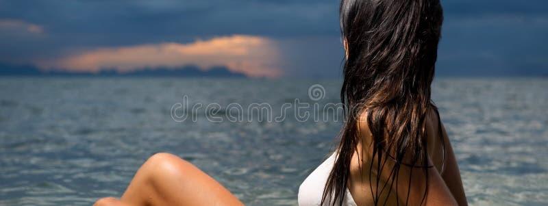 Morena bonita na água no por do sol imagem de stock royalty free