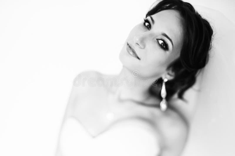 A morena bonita no vestido branco olha segura e sedutor fotografia de stock royalty free