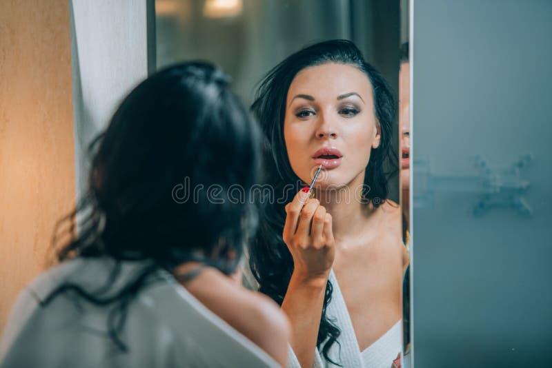 Morena bonita nova da mulher no banheiro, e roupão branco que faz a composição perto do espelho imagens de stock royalty free