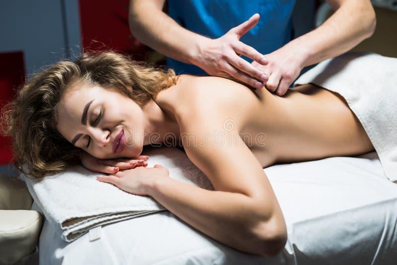 Morena bonita que aprecia uma massagem traseira que sorri na câmera nos termas da saúde Cuidados médicos fotografia de stock