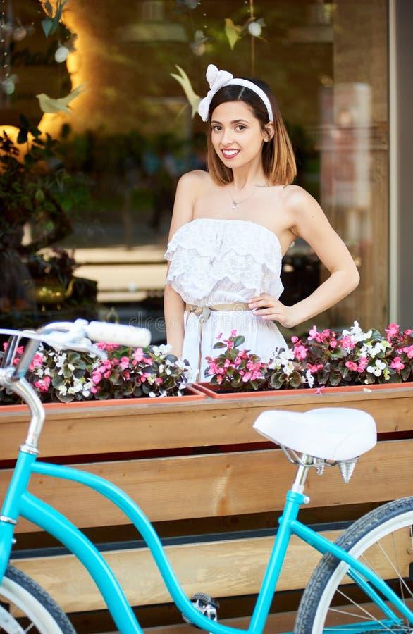 Morena bonita que levanta perto da bicicleta azul na frente do café confortável com as flores exteriores foto de stock