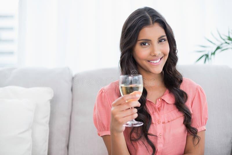 Morena bonito feliz que senta-se no sofá que guarda o vidro de vinho branco fotografia de stock