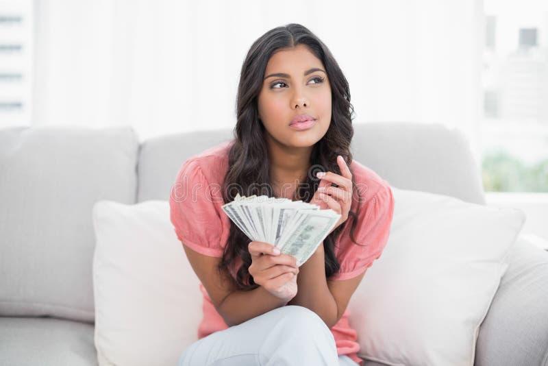 Morena bonito pensativa que senta-se no sofá que guarda o dinheiro fotos de stock