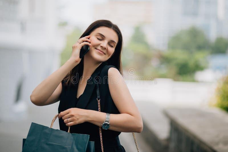Morena caucasiano bonita feliz nova da mulher com sacos de compras usando seu smartphone fotografia de stock