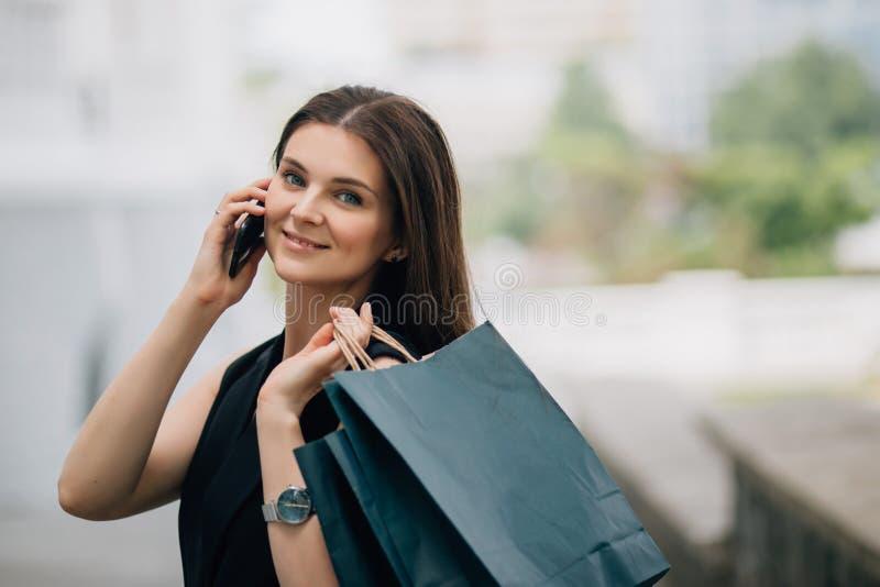 Morena caucasiano bonita feliz nova da mulher com sacos de compras usando seu smartphone foto de stock royalty free