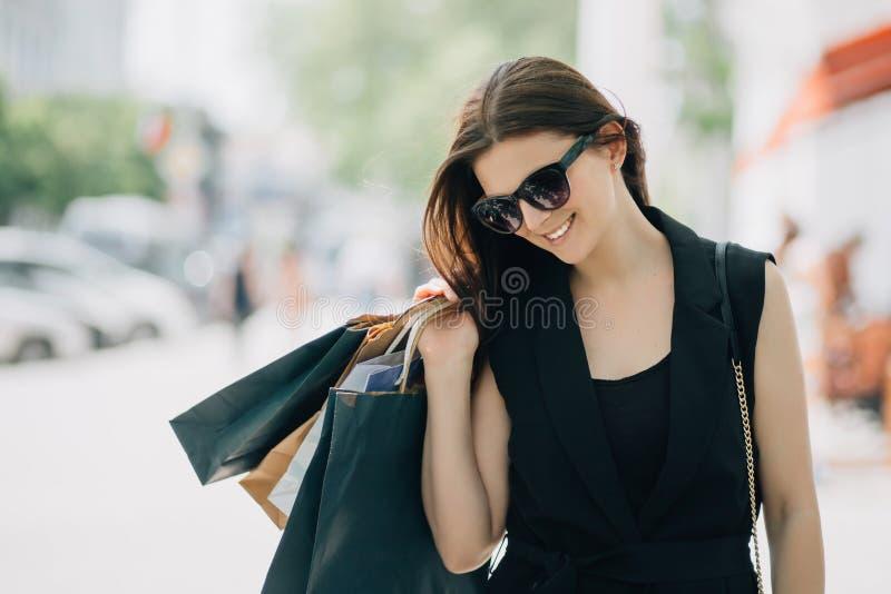 Morena caucasiano bonita feliz nova da mulher que sorri com os sacos de compras na rua foto de stock