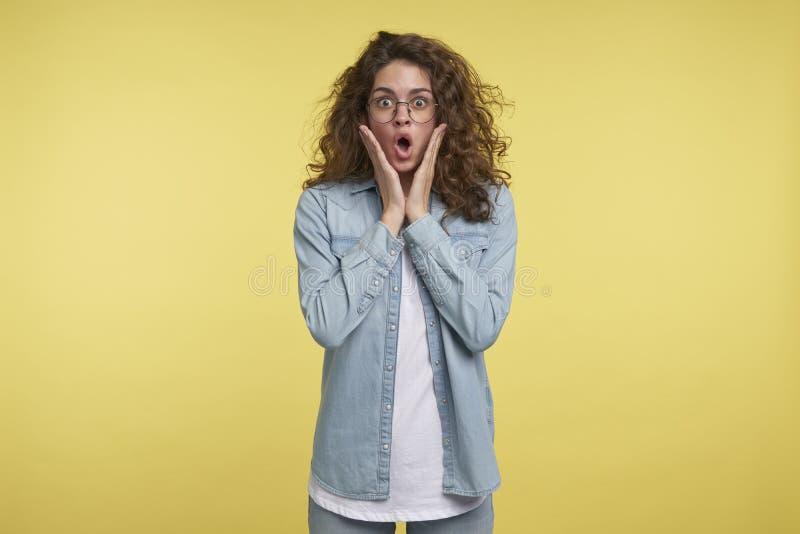 A morena chocou a mulher que está sendo surpreendida ver grandes discontos no mercado, sobre o fundo amarelo do estúdio imagem de stock