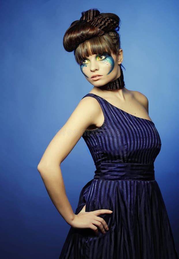 A morena com criativo compõe no vestido azul fotos de stock