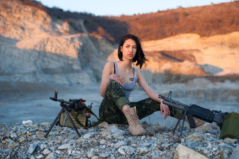Morena com uma metralhadora em um fundo das montanhas fotografia de stock