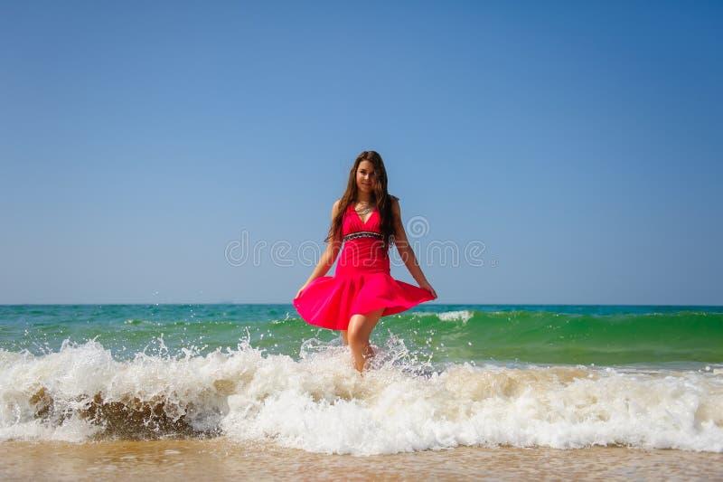 Morena de cabelos compridos 'sexy' nova na posição vermelha do vestido nas ondas com espuma branca no fundo do mar e o céu azul n imagem de stock royalty free