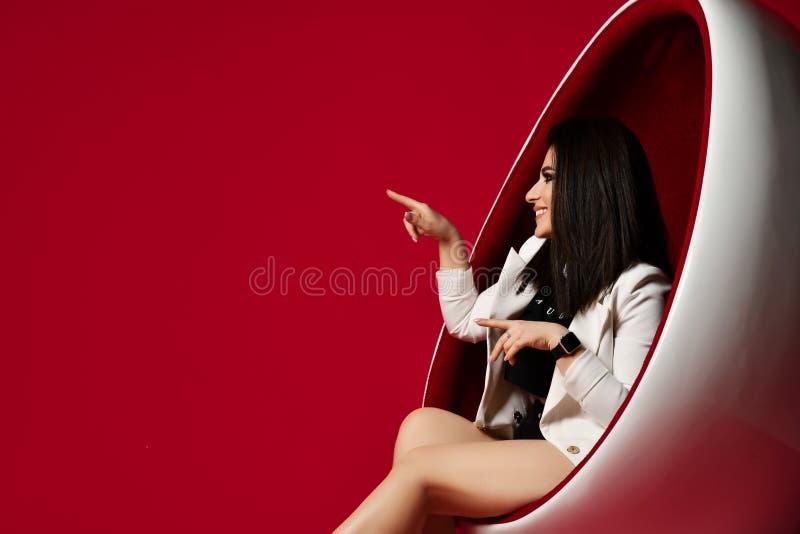 Morena de sorriso da mulher no revestimento longo branco que senta-se em uma cadeira oval moderna e em apontar seu dedo em algo n imagem de stock royalty free