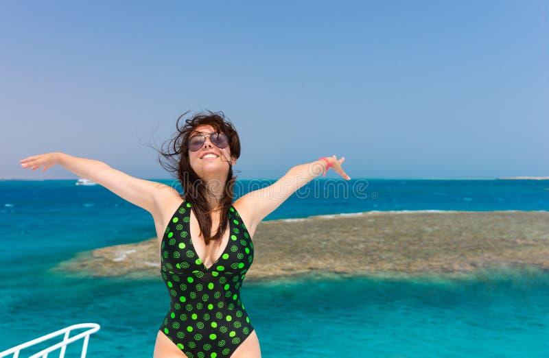 Morena de sorriso no roupa de banho preto-verde que está no iate a imagens de stock royalty free