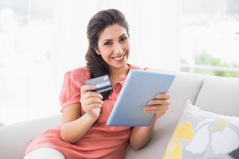 Morena de sorriso que senta-se em seu sofá usando a tabuleta para comprar em linha fotografia de stock