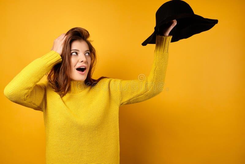 A morena de um suéter amarelo, abrindo a boca de surpresa, olha para o chapéu preto levantado em sua mão enquanto fotos de stock royalty free