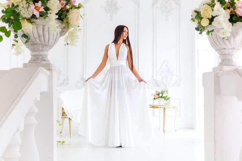 A morena delgada bonita está em um vestido branco fotos de stock royalty free