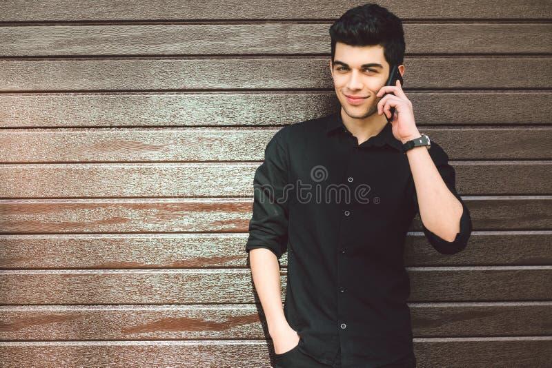 A morena do Oriente Médio turca do suspeito masculino considerável novo do modelo do retrato na camisa preta usa o telefone da  foto de stock