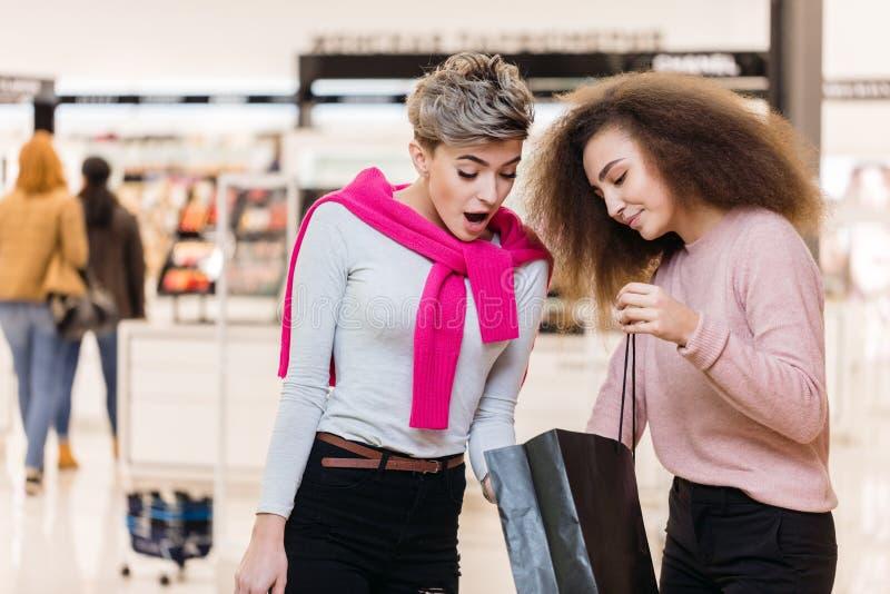 Morena e louro que olham o saco de compras entre si, discutindo compras imagem de stock