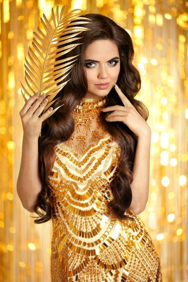 Morena elegante no vestido efervescente dourado Styl do encanto da forma fotos de stock royalty free
