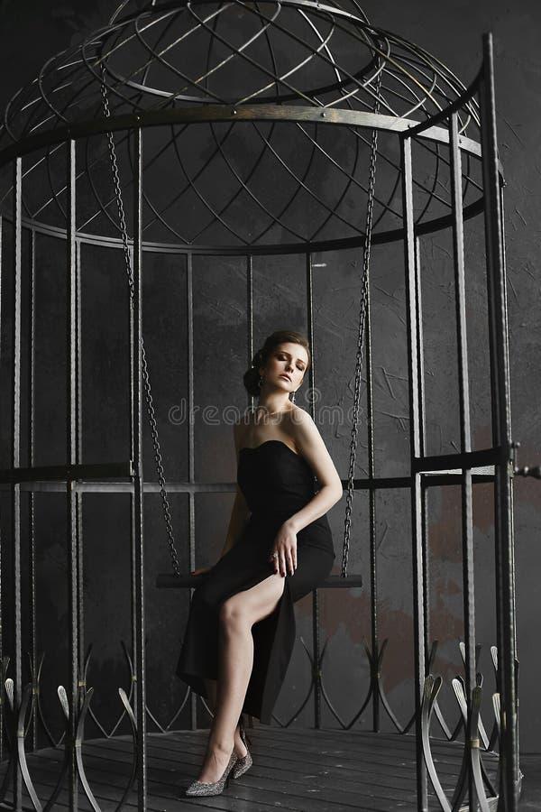 Morena elegante no vestido preto e levantamento no birdcage grande fotografia de stock