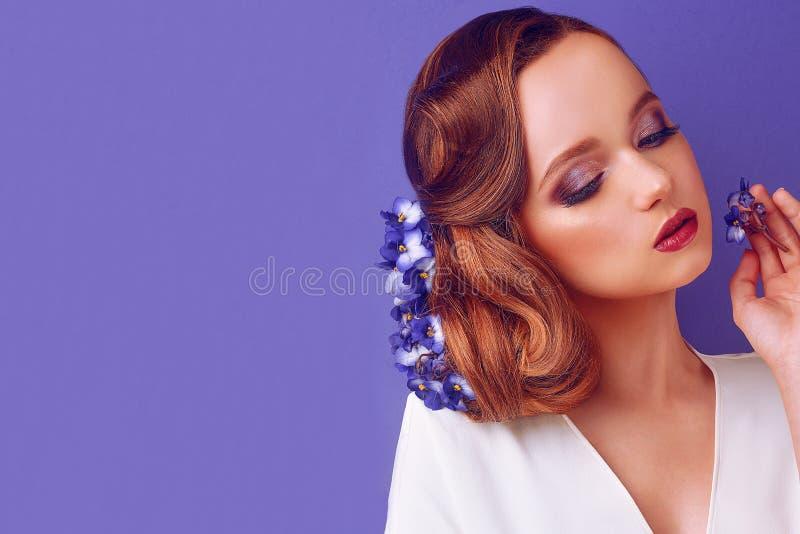 Morena em um fundo azul Menina com composição e penteado profissionais Sal?o de beleza de beleza Menina com as flores azuis em se imagem de stock