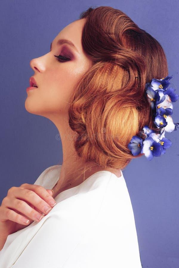 Morena em um fundo azul Menina com composição e penteado profissionais Sal?o de beleza de beleza Menina com as flores azuis em se fotografia de stock