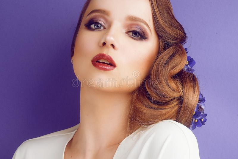 Morena em um fundo azul Menina com composição e penteado profissionais Sal?o de beleza de beleza Menina com as flores azuis em se fotos de stock royalty free