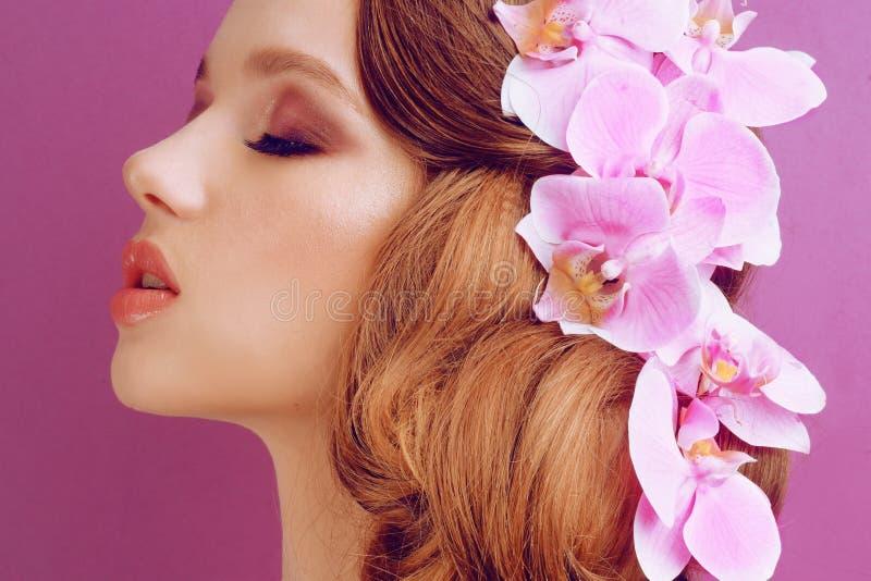 Morena em um fundo cor-de-rosa Menina com composição e penteado profissionais Cabelo que denomina, salão de beleza do vapor Bar d imagem de stock royalty free