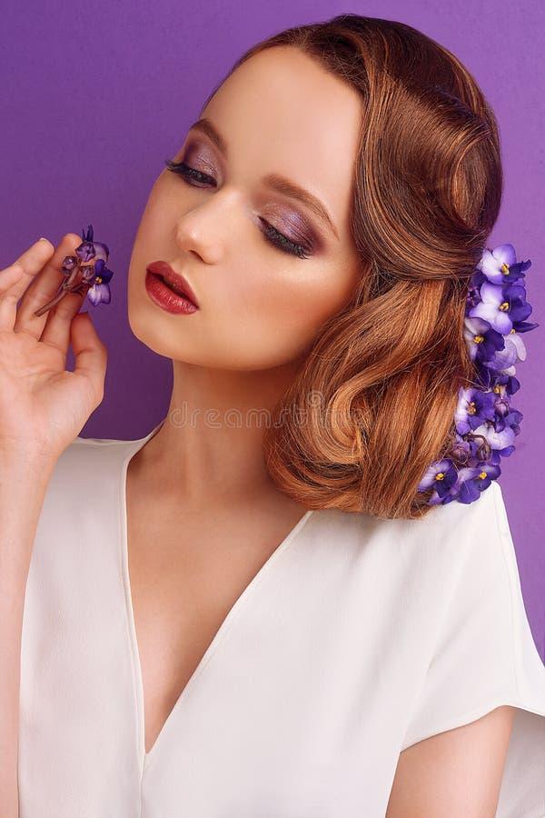 Morena em um fundo violeta Menina com composição e penteado profissionais Sal?o de beleza de beleza Menina com as flores azuis em fotos de stock