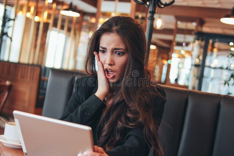 A morena encantador bonita preocupou a menina asiática assustado com a tabuleta na tabela no café fotos de stock royalty free