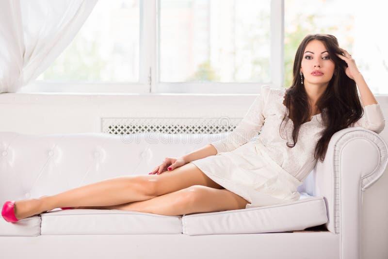 Morena encantador no sofá imagem de stock royalty free