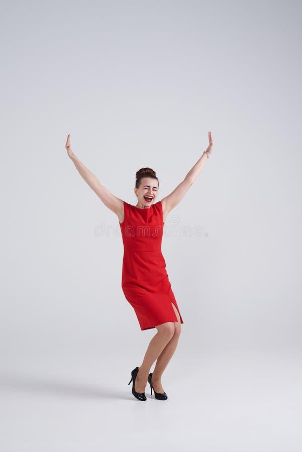 Morena entusiasmado nas mãos outstretching do vestido vermelho fotografia de stock