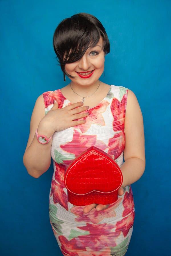 Morena feliz bonita com a caixa de presente vermelha da forma do coração no fundo contínuo do estúdio azul imagens de stock royalty free