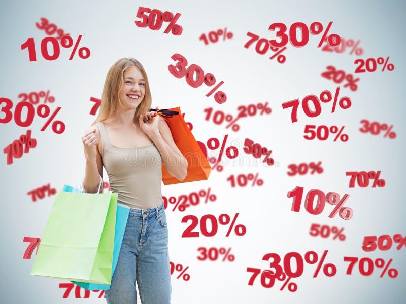 Morena feliz com os sacos coloridos Símbolos do disconto e da venda: 10% 20% 30% 50% 70% fotografia de stock