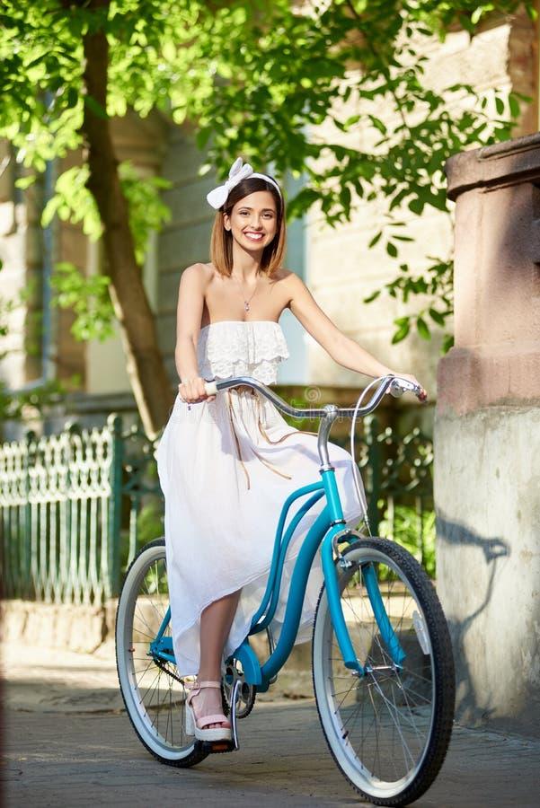 A morena feliz no vestido branco e na faixa que montam a bicicleta azul pavimentou para baixo a rua velha imagem de stock