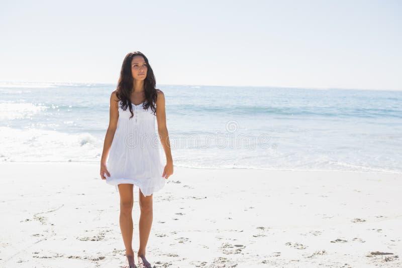 Morena feliz no vestido de sol branco que anda na areia fotografia de stock