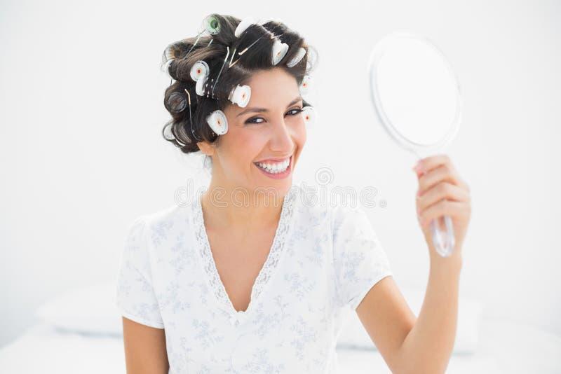 Morena feliz nos rolos do cabelo que guardaram o espelho de mão que sorri no Ca fotografia de stock royalty free